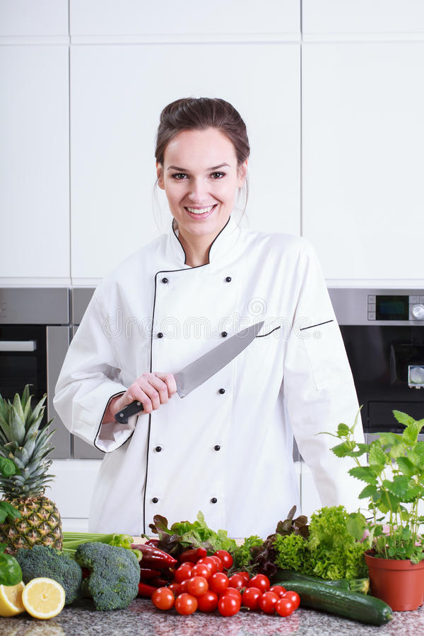 Lycklig damkock som förbereder mat royaltyfri fotografi
