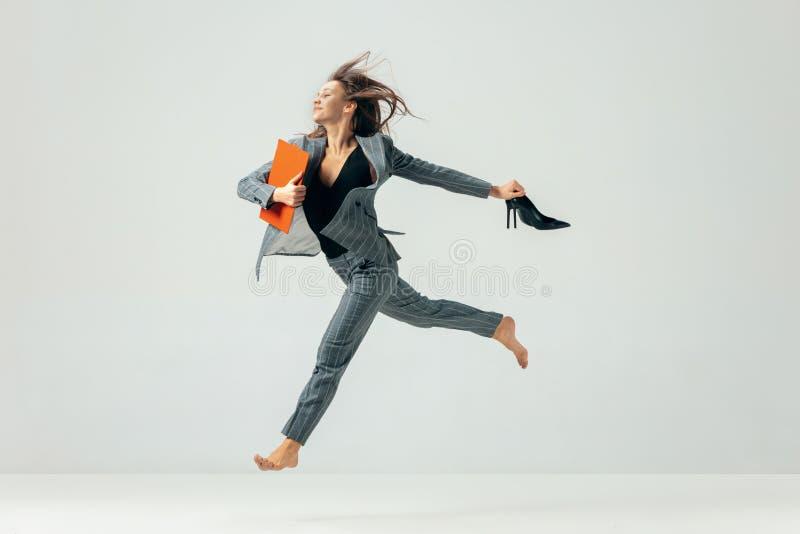 Lycklig dans för affärskvinna och le över vit royaltyfri bild