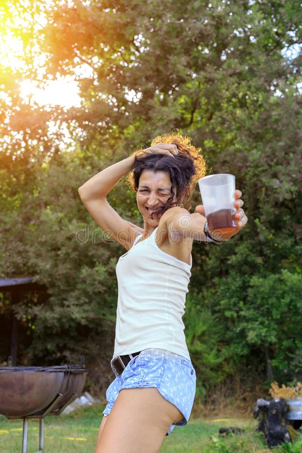 Lycklig dans för ung kvinna och hagyckel på sommarpartiet på solnedgången arkivfoton