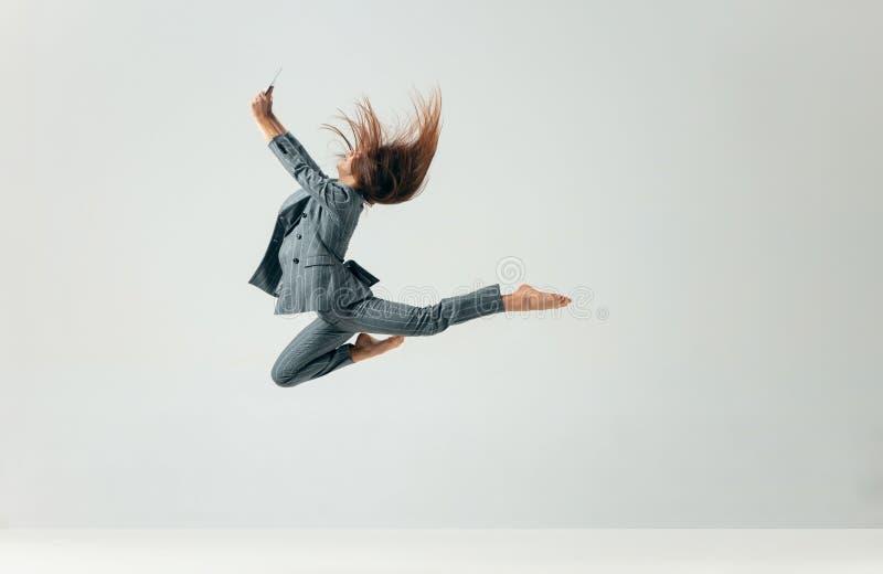 Lycklig dans och le för affärskvinna som isoleras över vit fotografering för bildbyråer