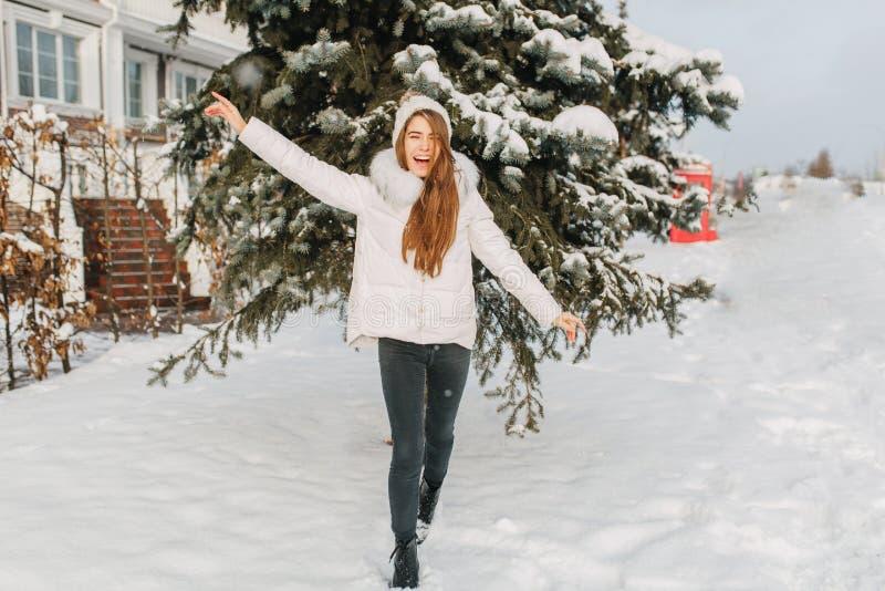 Lycklig djupfryst vintertid i solig morgon på gatan av den glade nätta flickan som har gyckel i snö uttrycka positivity royaltyfri foto