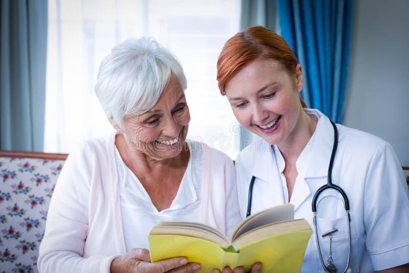 Lycklig doktor och patient som läser en bok royaltyfria bilder