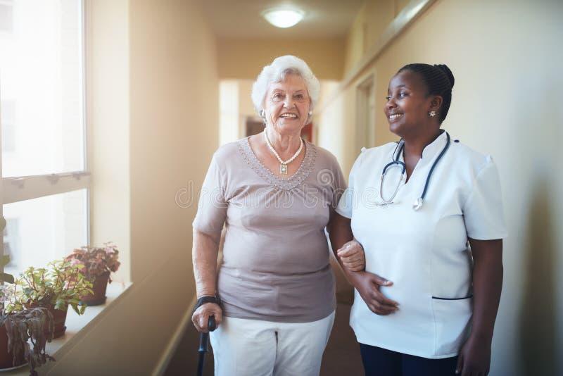 Lycklig doktor och patient tillsammans på vårdhemmet royaltyfri bild