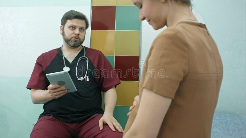 Lycklig doktor som har en cunsultation med gravida kvinnan, genom att använda den digitala minnestavlan arkivfoto