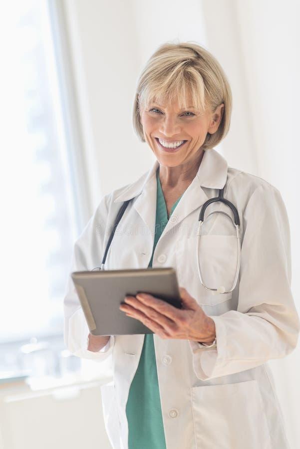 Lycklig doktor Using Digital Tablet i sjukhus arkivbild