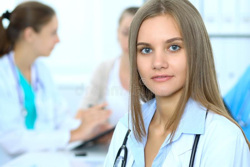 Lycklig doktorskvinna med den medicinska personalen på bakgrunden i sjukhuskontor royaltyfria foton