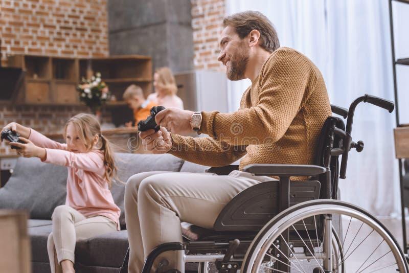 lycklig dotter och fader på rullstolen som spelar videospelet arkivfoton