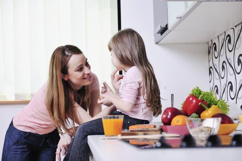 Lycklig dotter och mom i kök royaltyfria foton