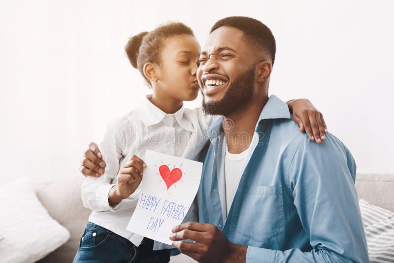 Lycklig dotter som kysser farsan och ger hälsningkortet royaltyfri fotografi
