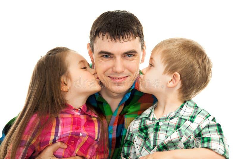 Lycklig doughter och son som kysser deras fader royaltyfri fotografi