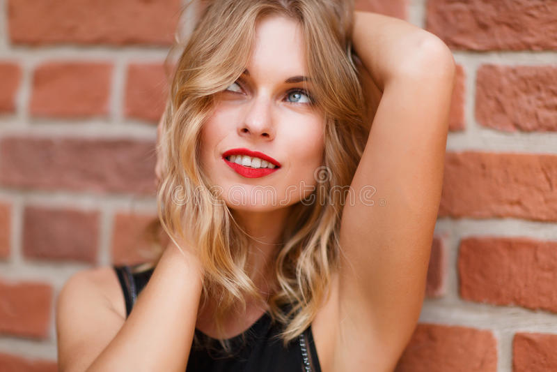 Lycklig drömlik blond kvinna med röd läppstift och sinnligt leende royaltyfri fotografi