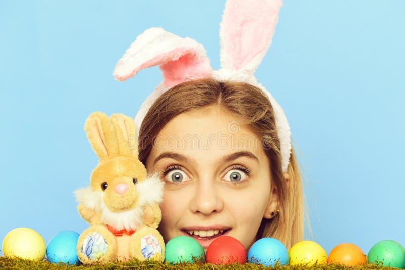 Lycklig easter flicka i kanin?ron med f?rgrika ?gg, kanin arkivfoton