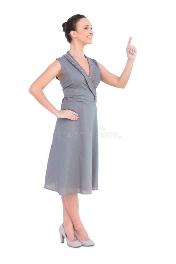 Lycklig elegant kvinna i flott klänning som pekar hennes finger royaltyfri bild