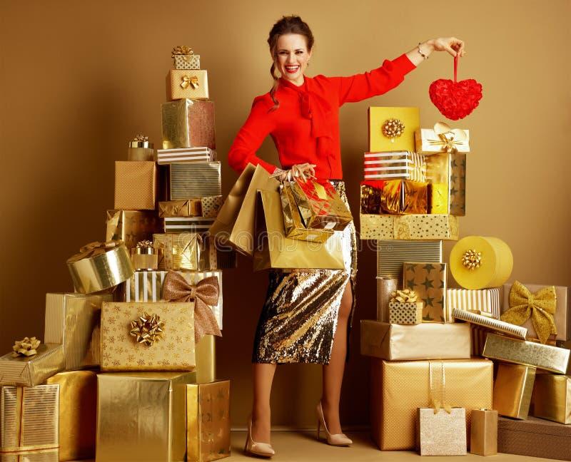 Lycklig elegant kvinna med shoppingpåsar som visar röd hjärta royaltyfria bilder