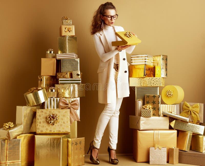 Lycklig elegant shopparekvinna som öppnar den guld- närvarande asken med pilbågen arkivfoton