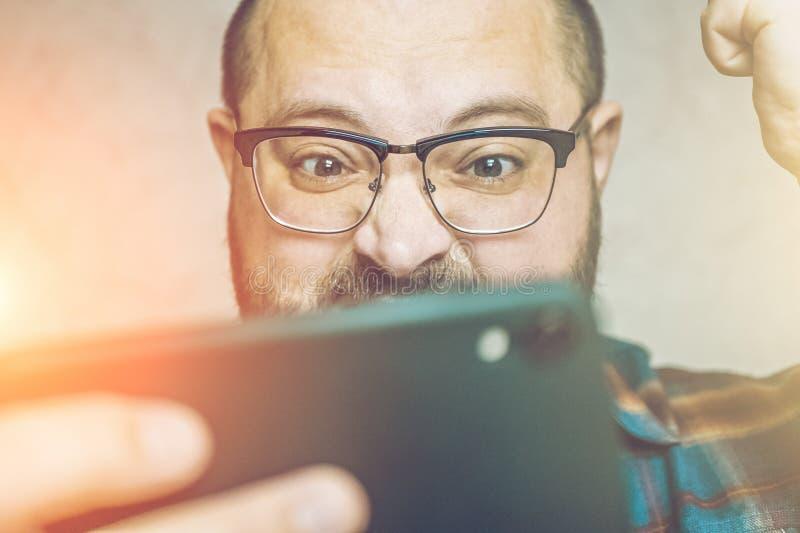 Lycklig emotionell man i exponeringsglasgester, når att ha segrat i mobil lek och att spela böjelse och affektion för smartphones arkivbild