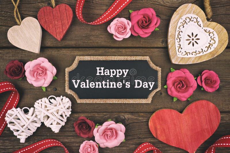 Lycklig etikett för svart tavla för valentindag med ramen av hjärtor och blommor royaltyfria foton