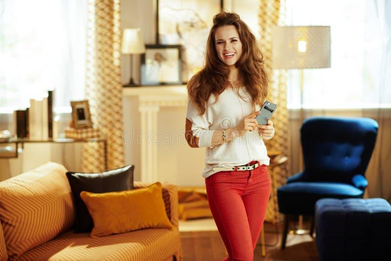 Lycklig färdig kvinna med smartphonen på det moderna hemmet arkivfoto