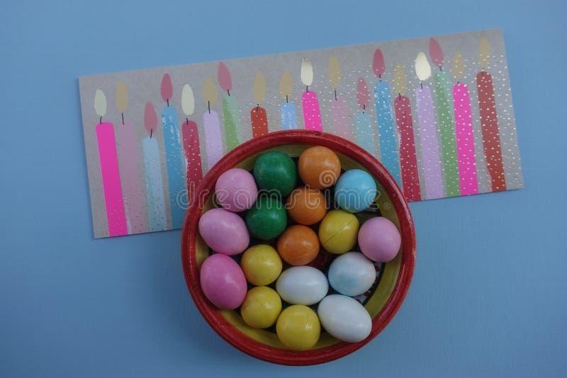 Lycklig födelsedag arton 18 år, roligt berömhälsningkort med stiliserade planlagda stearinljus, kulöra choklader och blå backgro vektor illustrationer