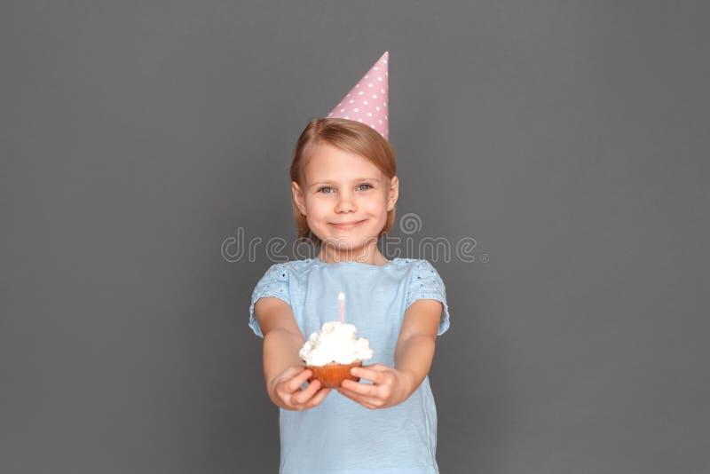 lycklig födelsedag Bärande lock för liten flicka som isoleras på den gråa geende muffin till att le för kamera som är gladlynt arkivbild