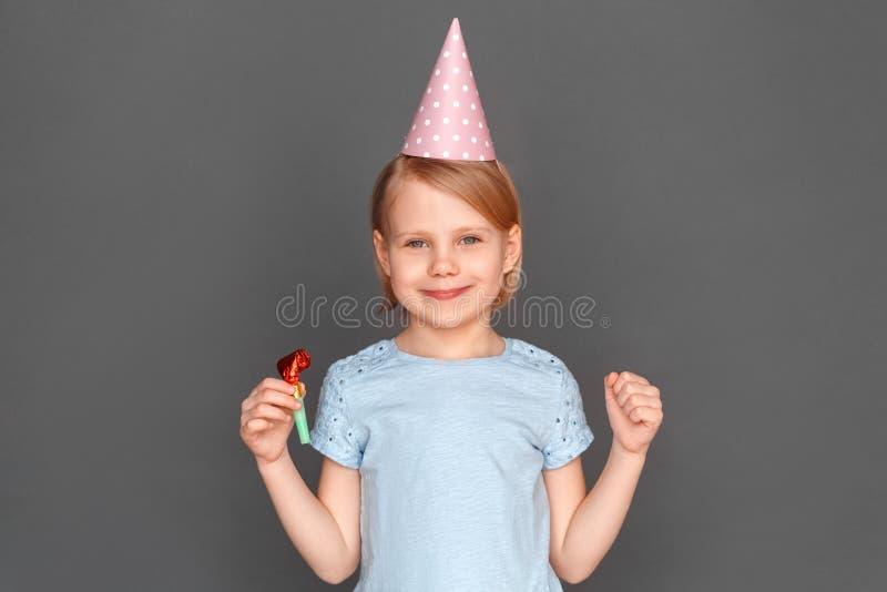 lycklig födelsedag Bärande lock för liten flicka som isoleras på grå färger med att le för partihorn fotografering för bildbyråer
