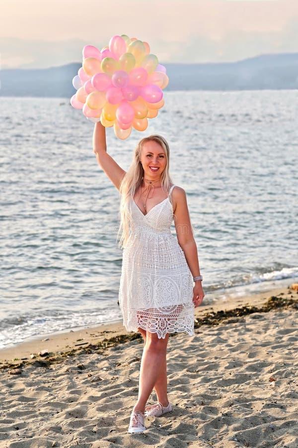 Lycklig födelsedag! Barn som ler den lyckliga kvinnan med färgrika ballonger på stranden som firar hennes födelsedag arkivbilder