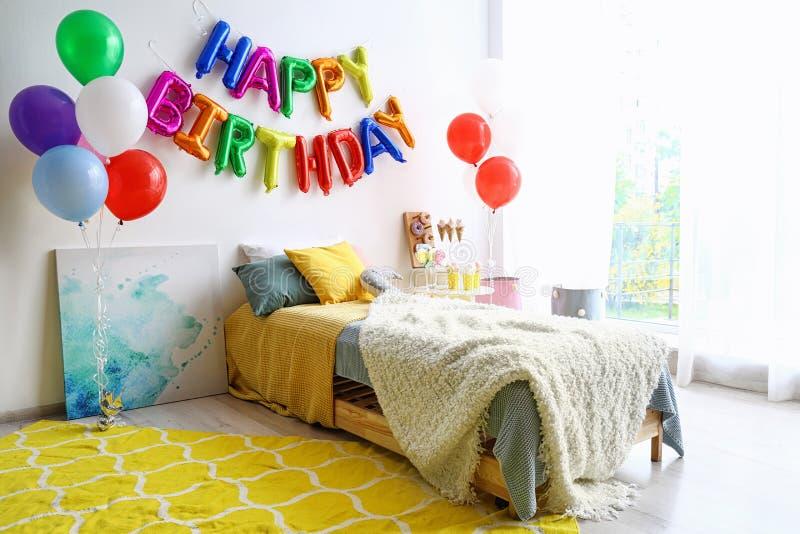 LYCKLIG FÖDELSEDAG för uttryck som göras av färgrika ballongbokstäver i sovrum royaltyfria foton