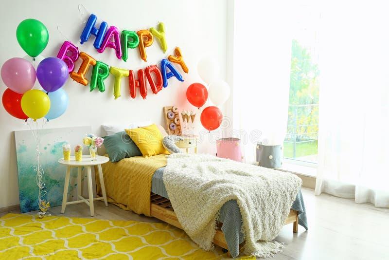 LYCKLIG FÖDELSEDAG för uttryck som göras av färgrika den ballongbokstäver och tabellen med fester i sovrum royaltyfria foton
