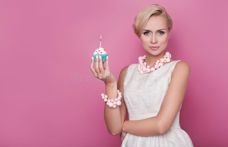 lycklig födelsedag Härliga unga kvinnor som rymmer den lilla kakan med den färgrika stearinljuset royaltyfria foton