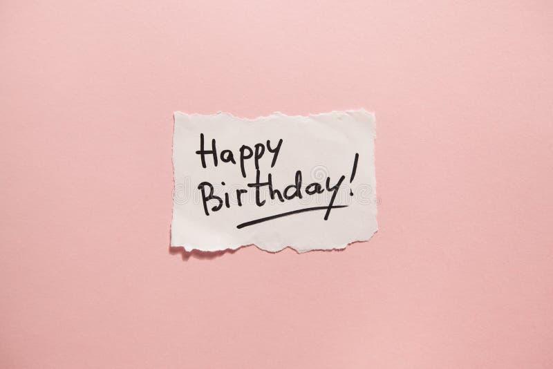 Lycklig födelsedag, papper med text på rosa bakgrund fotografering för bildbyråer