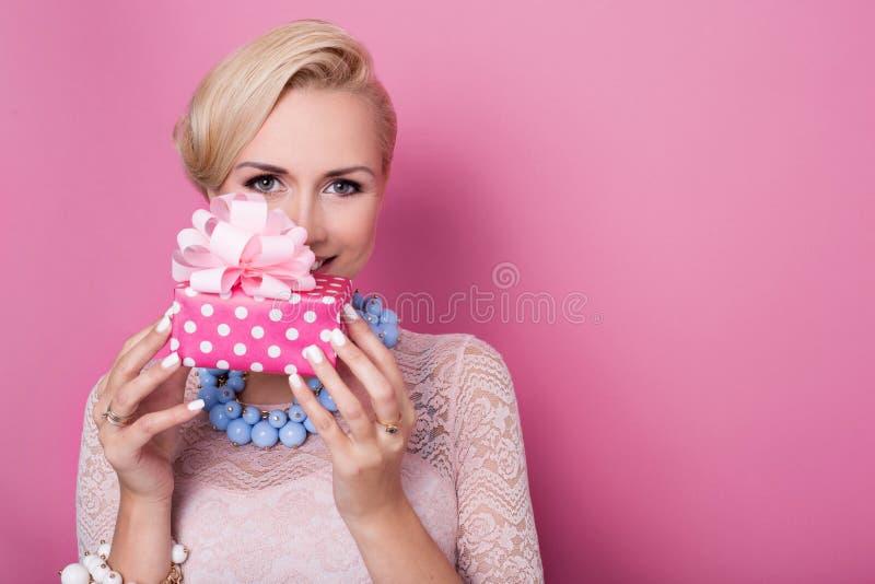 lycklig födelsedag Söt blond kvinna som rymmer den lilla gåvaasken med bandet soft för fält för färgpildjup grund royaltyfri bild