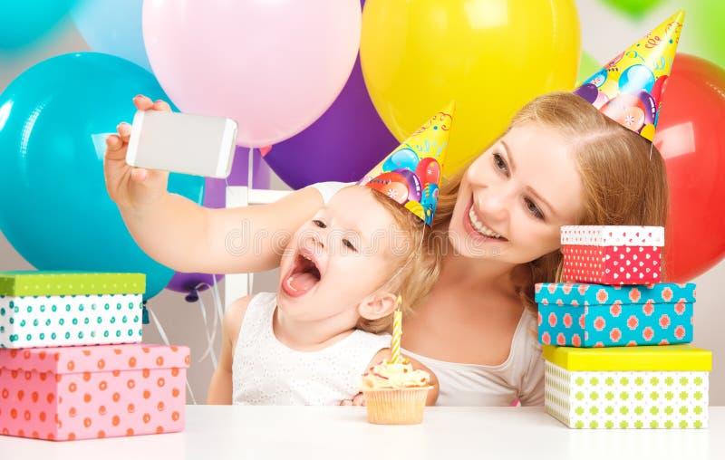 lycklig födelsedag Selfie modern fotograferade hennes dotter födelsedagbarnet med ballonger, kakan, gåvor royaltyfri bild