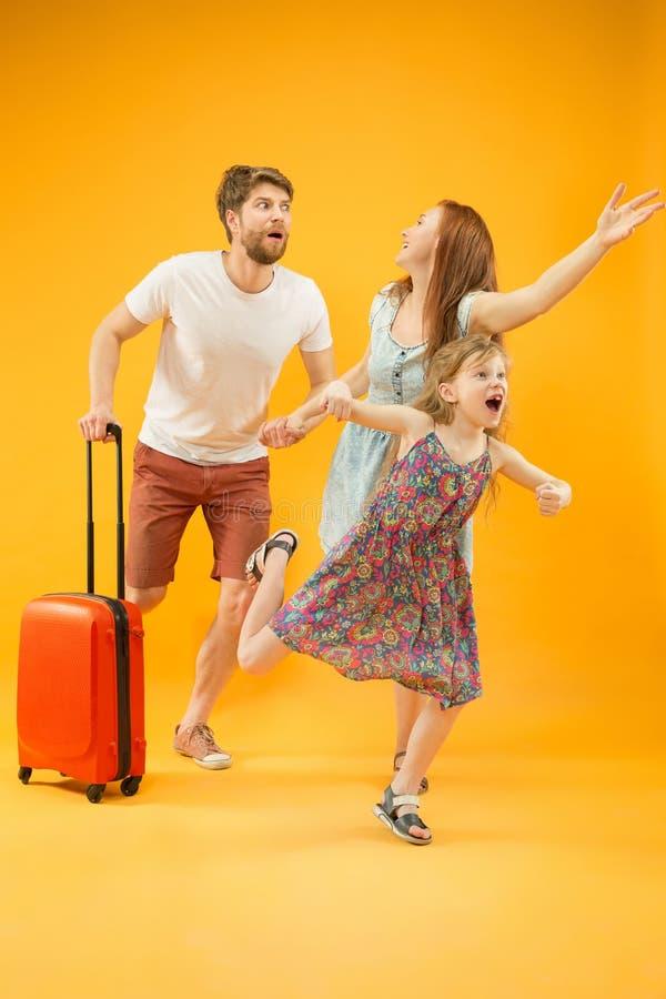 Lycklig förälder med dottern och resväskan på studion som isoleras på gul bakgrund arkivfoto