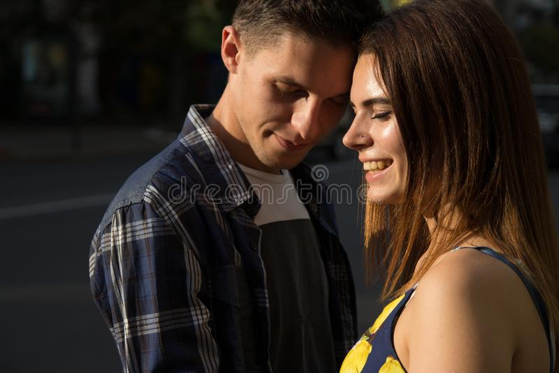 lycklig förälskelse för par flicka isolerad le white en man trycks på mot hennes kind, stängda ögon royaltyfria bilder
