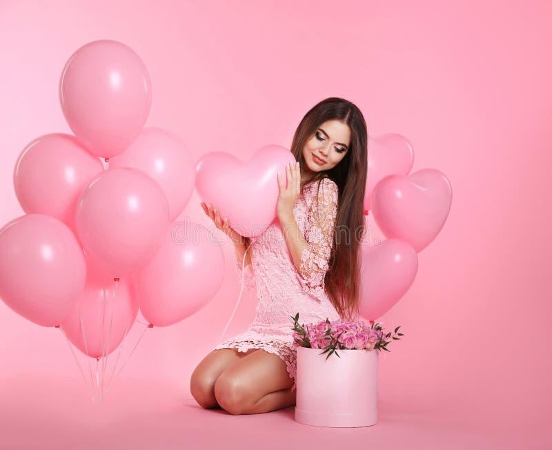 Lycklig förälskelsebrunettflicka med ballonger och buketten av rosa flowe arkivbilder