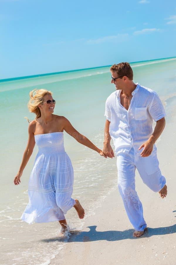 Lycklig för kvinnapar för ung man spring på en strand royaltyfri fotografi