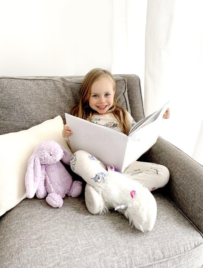 Lycklig förskole- flickaläsning arkivfoton