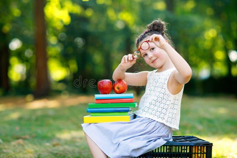 Lycklig förtjusande flickaläsebok för liten unge och olika färgrika böcker för innehav, äpplen och exponeringsglas på den första  royaltyfria bilder