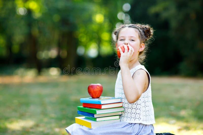 Lycklig förtjusande flickaläsebok för liten unge och olika färgrika böcker för innehav, äpplen och exponeringsglas på den första  royaltyfri foto