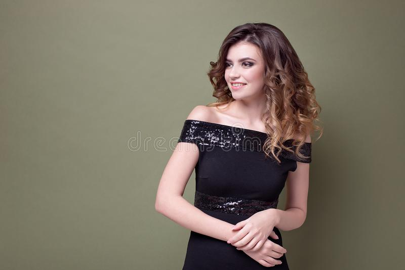 Lycklig förtjust kvinnlig med det positiva leendet, leenden i huvudsak, iklädd svart klänning med paljetter, över den gröna vägge arkivbild