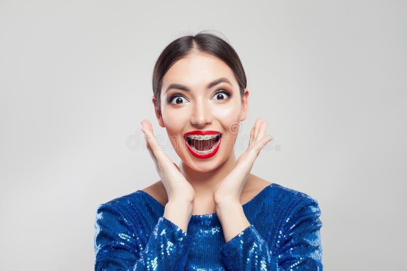 Lycklig förvånad kvinna i hänglsen på tänder på vit bakgrund Upphetsad flicka med hänglsen som har gyckel fotografering för bildbyråer