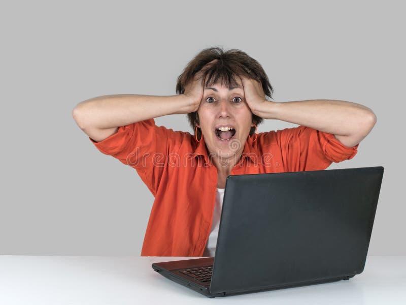 Lycklig förvånad kvinna på bärbara datorn Emailgoda nyheter! Ljus apelsin royaltyfria bilder