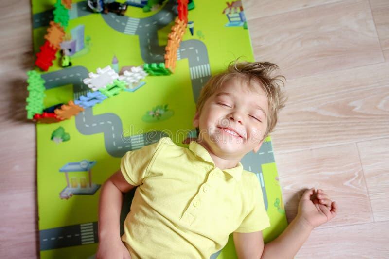 Lycklig f?rskole- ?lderbarnlek med f?rgrika plast- leksakkvarter Id?rika dagisungar bygger ett kvartertorn arkivfoto