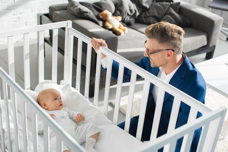 lycklig fader i formella kläder som sitter nära begynnande dotter royaltyfri fotografi