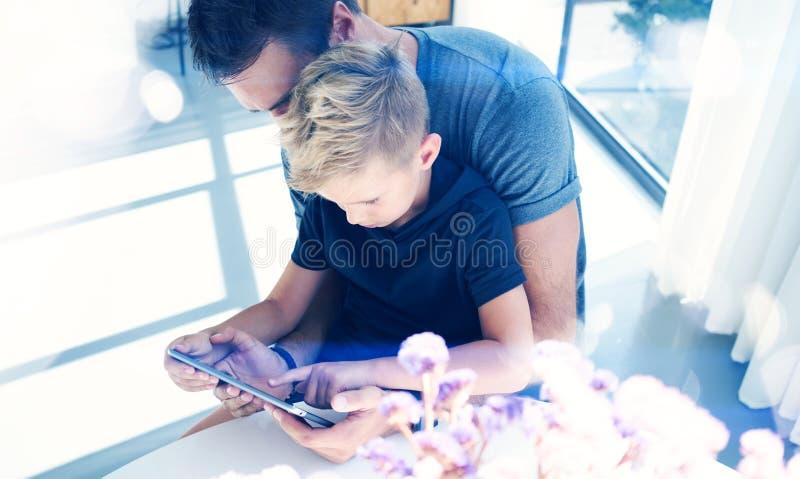 Lycklig fader med den unga sonen som använder minnestavlaPC i soligt hem Farsa och pys som spelar på den mobila datoren som inomh royaltyfria bilder
