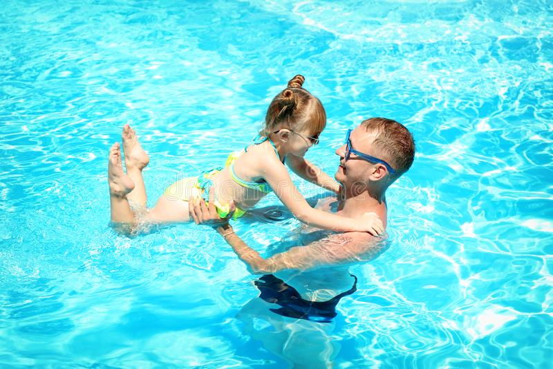 Lycklig fader med dottern som spelar i simbassäng royaltyfri foto