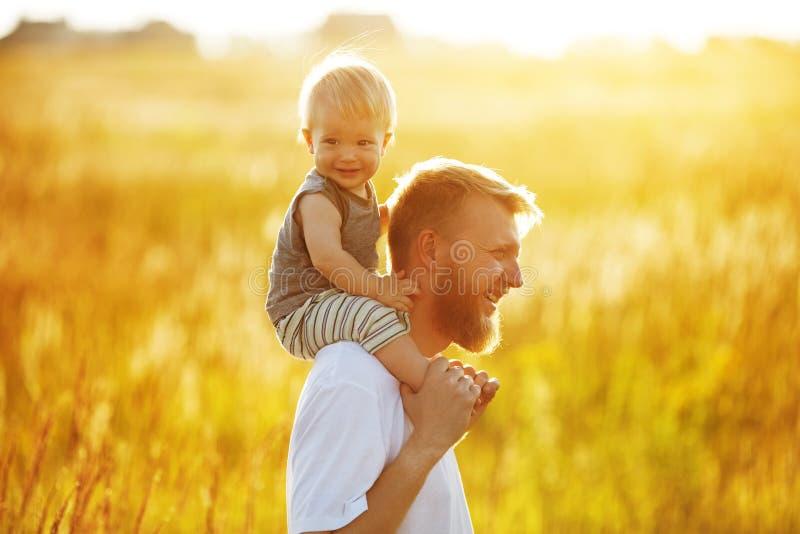 Lycklig fader med hans lilla son på hans skuldror arkivbild