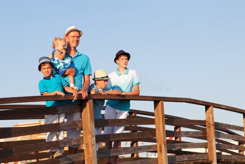 Lycklig fader med hans söner och litet dotteranseende på träbron royaltyfria foton