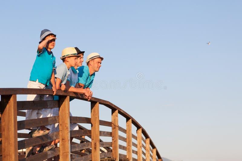 Lycklig fader med hans söner som står på träbron arkivfoto