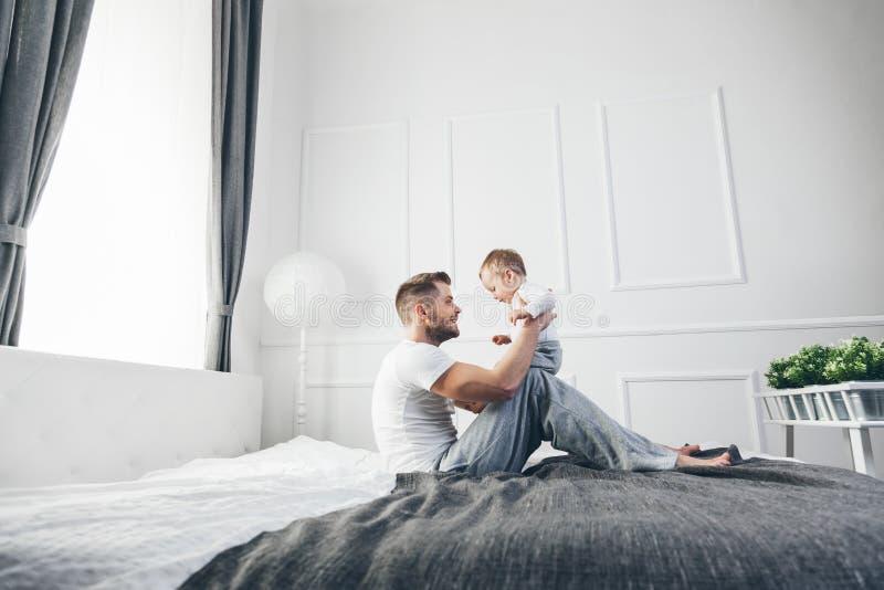 Lycklig fader med hans son som hemma spelar på sängen arkivbilder